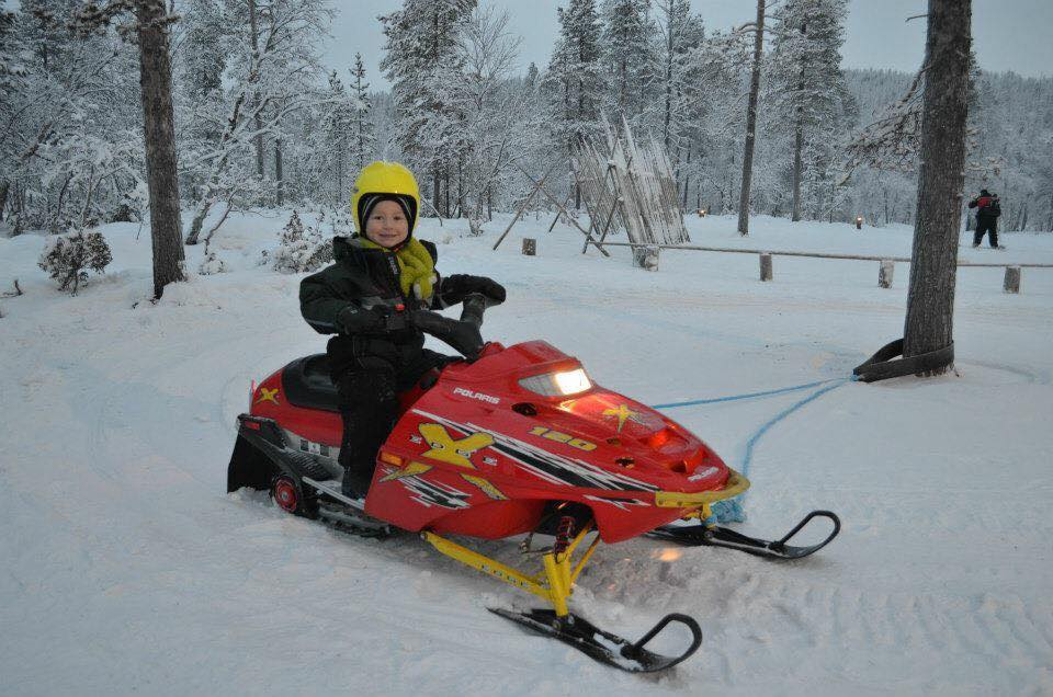 Cayden riding a skiddo in Lapland